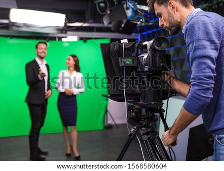 Presenters and video camera operator working in studio. News broadcasting