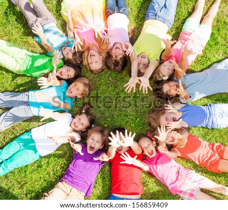 14 kids laying in a circle in the grass with happy faces shoot from above lifting hands above  #156859409