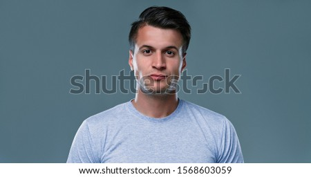 Unshaven confident serious young male enterpreneur with attractive appearance dressed casually as spends weekends at home, isolated over gray background. Stylish handsome guy indoor. #1568603059