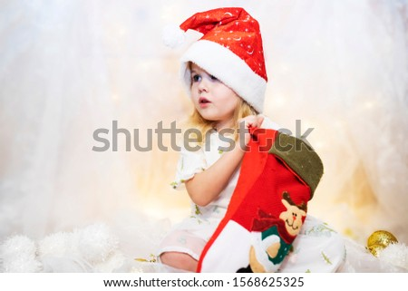 Surprised cute child girl opening a Christmas present. It's Christmas time! Adorable little girl open her stocking gifts on Christmas morning. Xmas holidays concept.