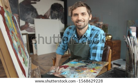 Portrait of young handsome male artist at work sitting at the easel with a palette