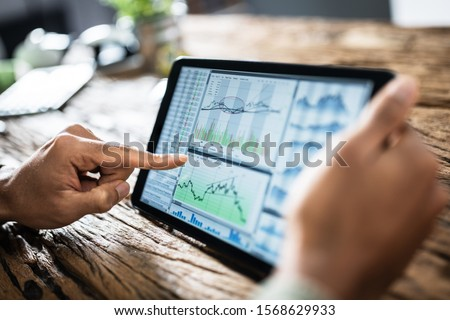 Close-up Of Businessman Analyzing Stock Market Status On Digital Tablet Royalty-Free Stock Photo #1568629933