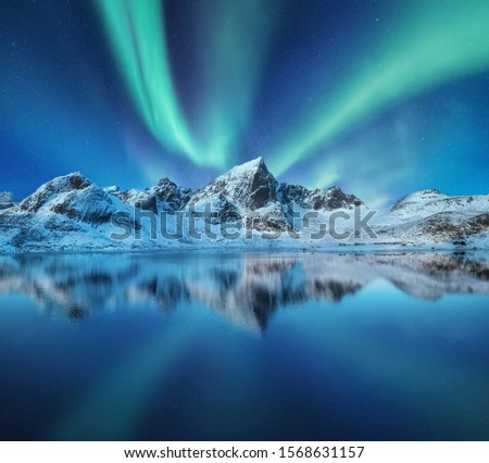 Mountains and northern lights in the sky. Reflections of the night sky and mountains on the water. Winter landscape in Norway #1568631157