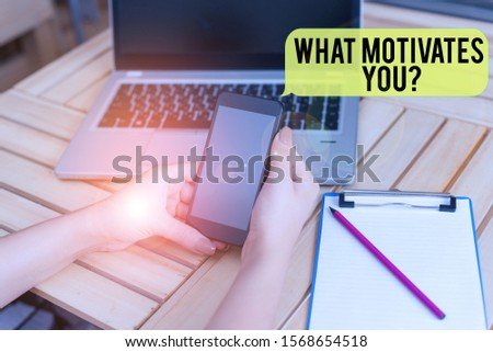 Handwriting text What Motivates Youquestion. Concept meaning know reasons why you want to wake up each morning woman laptop computer smartphone office supplies technological devices. #1568654518