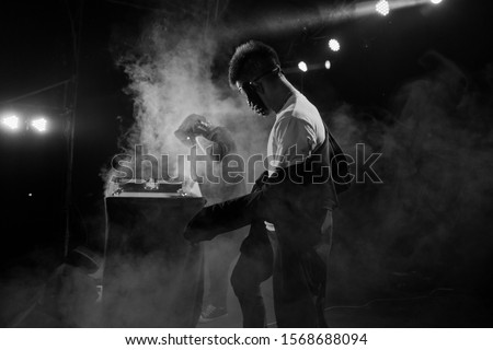 Professional dancers - young white guys in masks is dancing emotional inflammatory club dance on stage during a dubstep party, DJ, black and white, rhythm, tempo, movement, happiness, performance, PJ #1568688094