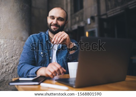 Smiling content bearded man holding glasses and looking at camera while sitting at table with coffee cup and laptop at street terrace #1568801590