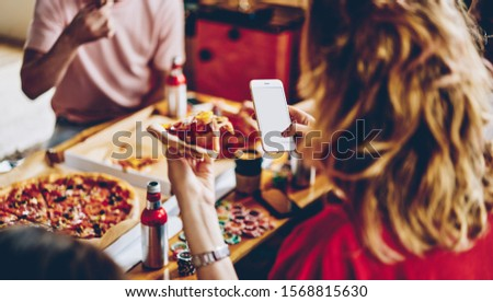 From above appetizing piece of pizza in hand of crop woman taking photo on mobile phone eating with group of multiracial people at table #1568815630