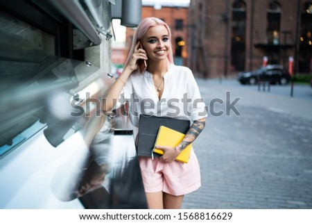 Young happy fashionable female in white shirt and rose shorts talking on mobile phone while walking in street with notebook and documents and looking at camera #1568816629