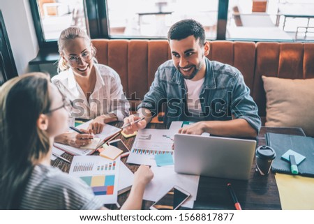 From above cheerful man smiling and talking with female colleague while sitting at table and working with graphs in modern restaurant #1568817877