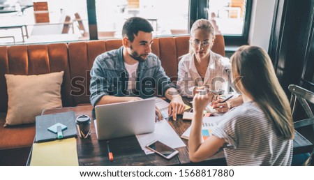 From above young bearded freelancer talking with female coworkers about business project while sitting at table and doing remote job in cozy cafe together #1568817880