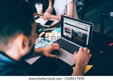 Young bearded male in casual jeans apparel watching laptop sitting at wooden table loaded with  documents stickers smartphone in office with colleagues #1568817898