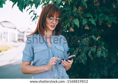 Smiling caucasian woman in eyewear enjoying downloaded audiobook on smartphone and earphones, millennial female blogger using devices and accessories for listening playlist songs on street  #1568819812