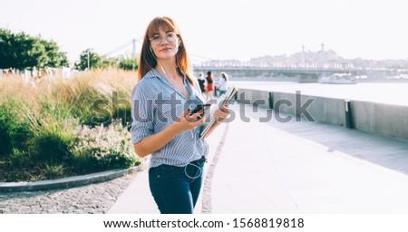 Positive redhead female student walking in earphones enjoying favorite songs on mobile phone, charming hipster girl listen audiobook downloaded on smartphone strolling on urban settings on sunny day  #1568819818