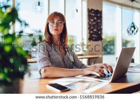 Attractive redhead woman in eyewear for vision protection working remotely typing publications sitting in cafe, pensive caucasian female freelancer look away browse on laptop computer during job  #1568819836