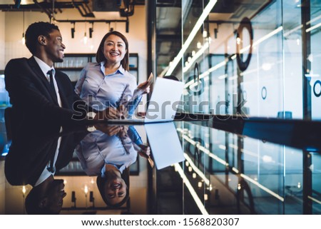 African American businessman and Asian businesswoman talking and having fun while sitting together in front of laptop at reflective counter in modern office  #1568820307