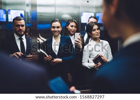 Reflection of group of smiling pleased people in suits carrying documents and taking pictures with smartphone while standing together in elevator cabin at urban office building