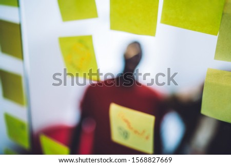 Glass with adhesive yellow memo stickers and blurred coworkers standing behind glass wall in modern office space creating plan #1568827669