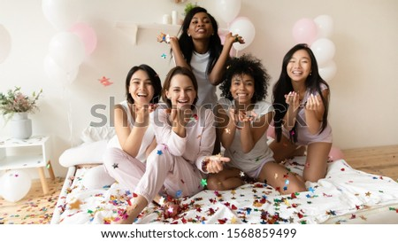 Happy diverse young ladies wear pajamas sit on bed look at camera hold confetti, smiling multiracial girls friends group celebrating bachelorette slumber party bridal shower with balloons, portrait #1568859499