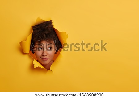 Photo of attractive curly African American woman looks with curious expression aside, notices something interesting, has natural beauty, isolated over yellow background in paper hole, has fun indoor Royalty-Free Stock Photo #1568908990