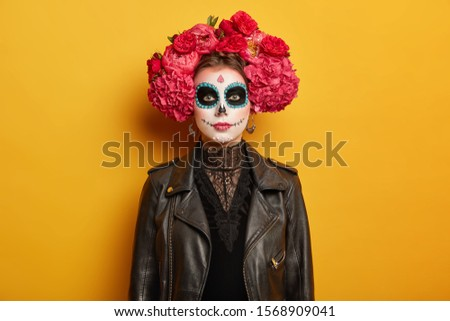 Portrait of beautiful serious woman has creative vivid makeup, wears flower wreath, black clothes, tries be scarying, comes on Halloween holiday party or Day of Dead, isolated over yellow background #1568909041