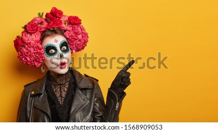 Shocked female wears creative sugar skull makeup, wreath made of red peonies, celebrates All Souls day, holiday in Mexico points away with index finger isolated over yellow background shows copy space #1568909053