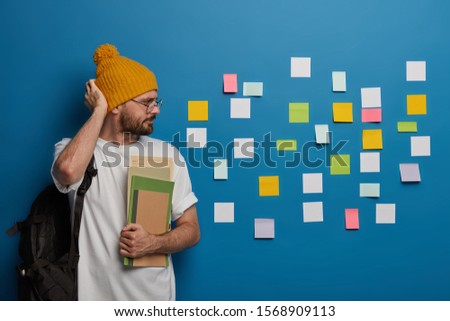 Serious hipster rubs head, looks seriously at colorful notes stuck on wall, recalls necessary information, carries rucksack and textbooks, thinks how to make startup project, studies week schedule #1568909113