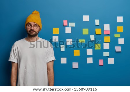 Indoor shot of serious contemplative man with beard, dressed casually, thinks about writing diploma, uses adhesive notes to write down information to remember. Male manager plans working day #1568909116