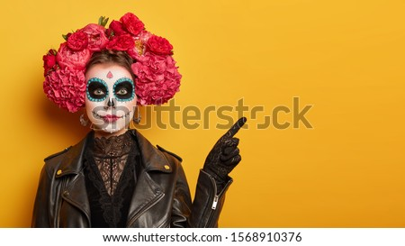 Mexican culture, Day of Death concept. Serious woman with bright scary makeup, flower wreath, dressed in black leather jacket, points aside on yellow copy space , shows place of Halloween party #1568910376