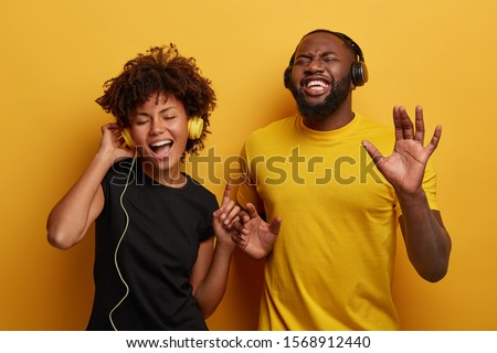 Happy girlfrind and boyfriend sing song and dance with rhythm of music, listen favourite songs in headset, enjoy new track, wear casual clothes, isolated over yellow wall. Lets have fun together #1568912440
