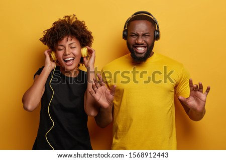 Lively energetic dark skinned couple dance and have fun together, smile from joy, listen different types of music in headphones, wear black and yellow clothes, isolated on bright background. #1568912443