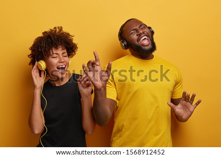 Studio shot of overjoyed teenage couple dance with raised hands, enjoy cool music in stereo headphones, listen pleasant popular track, move actively against yellow background, feel happy and great #1568912452