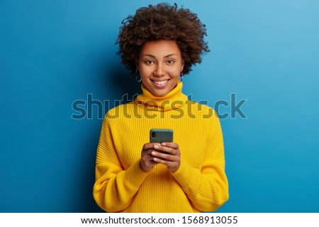 Adorable dark skinned adult woman dressed in yellow jumper, holds mobile phone, browses social networks, has broad smile, enjoys online chatting, isolated on blue wall, being always in touch #1568913055