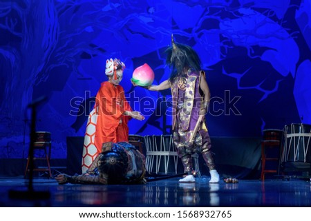 Traditional Japanese performance. Actors in traditional costumes perform on a stage. Dead samurai lay and woman talks with demon. #1568932765