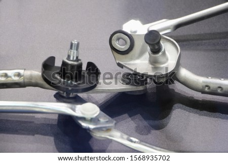 Car wiper drive mechanism, rods and joints close up on gray background #1568935702