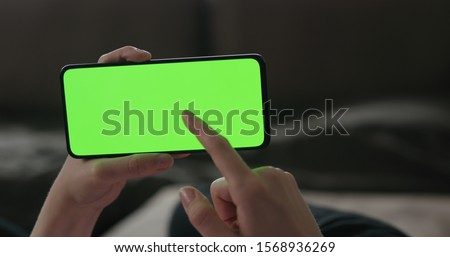 Young woman lying on a couch and using smartphone with horizontal green screen