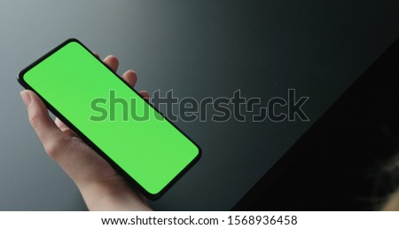 Young woman sitting on a chair near window and using smartphone with green screen