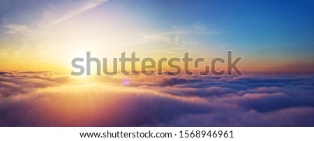 Beautiful sunset cloudy sky from aerial view. Airplane view above clouds #1568946961