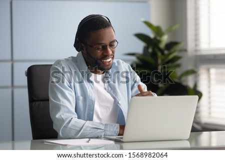 Happy african American male worker wearing headphones speak on video call using laptop, smiling biracial young businessman in earphones have business conference with client at computer online #1568982064