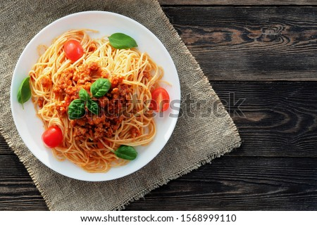 Spaghetti bolognese served on a white plate on a dark wooden background with tomatoes and basil #1568999110