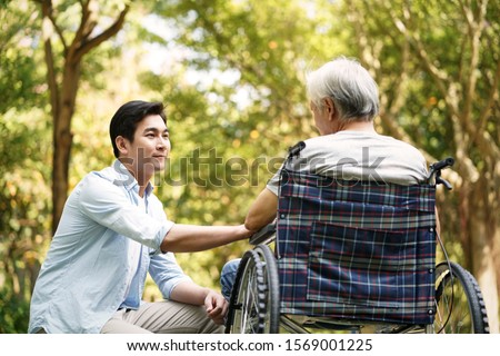 asian son talking to and comforting wheelchair bound father #1569001225