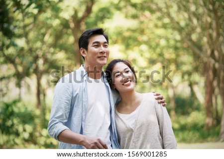 happy loving young asian couple relaxing in park