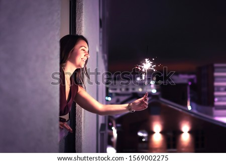 Sparkle in the night. Woman holding a sparkler out of window. New Year's Eve, Christmas party or birthday celebration at home. Happy elegant lady celebrating. City view. Light from firework stick. #1569002275