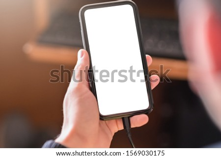 Man hand holding smartphone and use device and charging device while using with blank white screen for mockup #1569030175