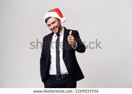 Young handsome caucasian guy in business suit and Santa hats on white background in studio smilie and showing thumbs up two hands. Close up portrait business person with Christmas mood Holiday banner #1569031936
