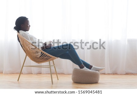 Relax at home. African american girl resting in wicker armchair and drinking coffee against window, free space #1569045481
