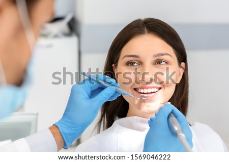 Smiling pretty woman looking with trust at dentist doctor during treatment #1569046222