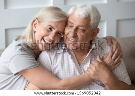Head shot close up portrait happy grey haired middle aged woman snuggling to smiling older husband, enjoying tender moment at home. Bonding loving old family couple embracing, feeling happiness. #1569052042