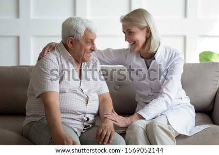 Friendly mature general practitioner communicating with pleasant 80s male patient, sitting together on sofa. Smiling trustful middle aged doctor giving psychological help to elder man at home visit. #1569052144