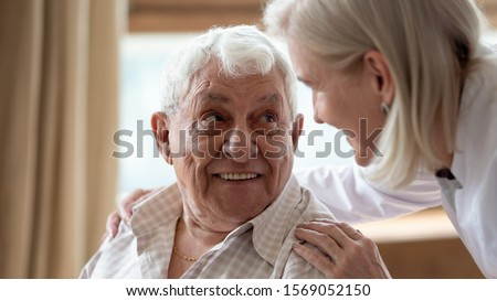 Head shot close up cheerful elderly man looking at pleasant middle aged nurse. Mature female doctor embracing shoulders, communicating with smiling 80s patient, giving support and psychological help. #1569052150