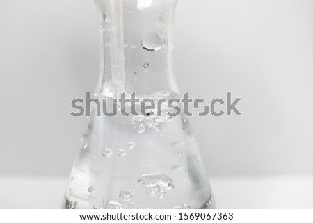 Closeup of a glass erlenmeyer flask with a plastic pipette in it with bubbles in the liquid on a white background. Science. #1569067363